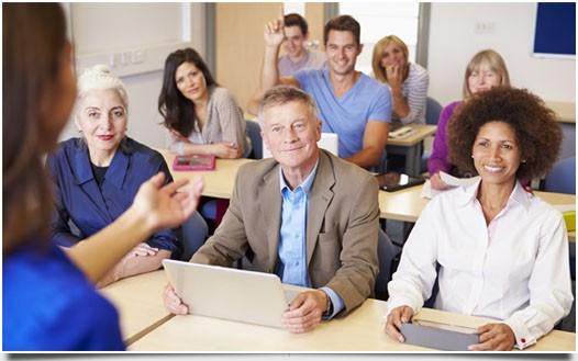 Menschen unterschiedlichen Alters lernen gemeinsam an Notebooks und Tablet-PCs